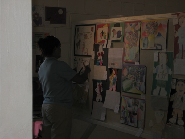 Person looks at some of the student art.