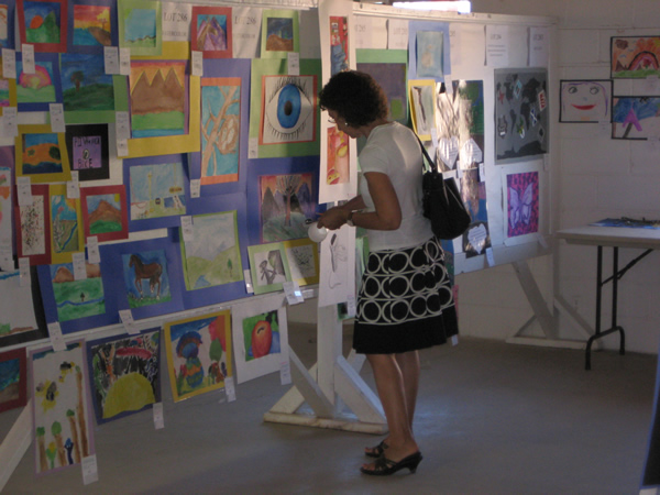 A spectator looks closely at some art.