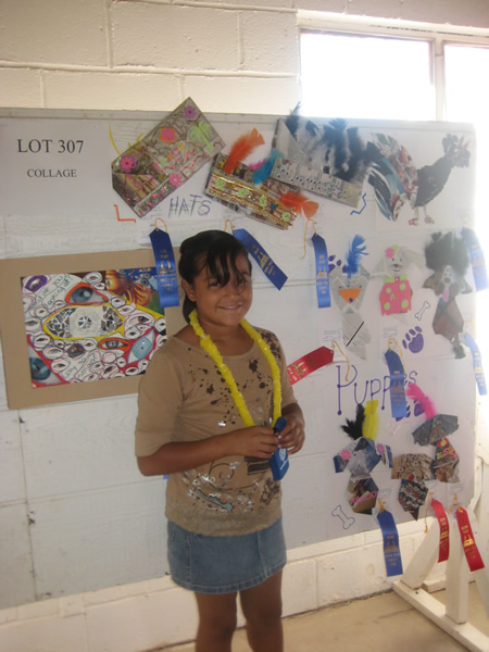 Student stands in front of her collage of ribbons and puppies.