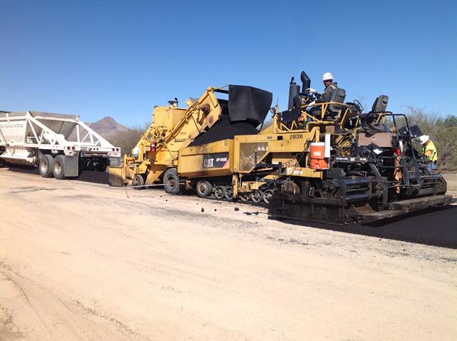 The machines place fresh asphalt for a new road.