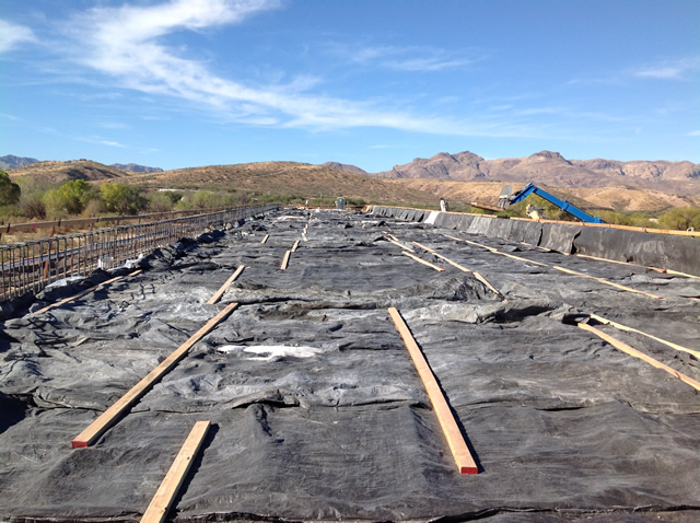 Black tarps cover the newly poured bridge deck in order to prevent cracking.