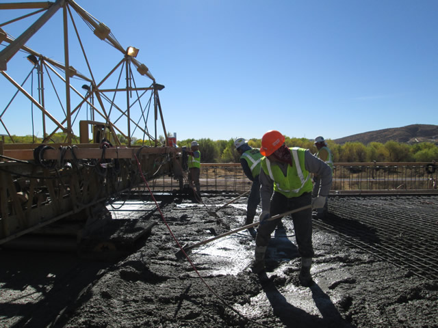 Public workers spread the concrete as it gets poured onto the bridge.